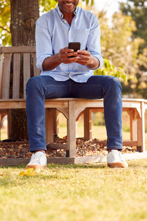 Close Up Of Man Sitting On Bench Under Tree In Summer Park Using Mobile Phone