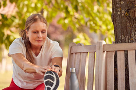 Woman Wearing Fitness Clothing Stretching And Warming Up On Seat Under Tree