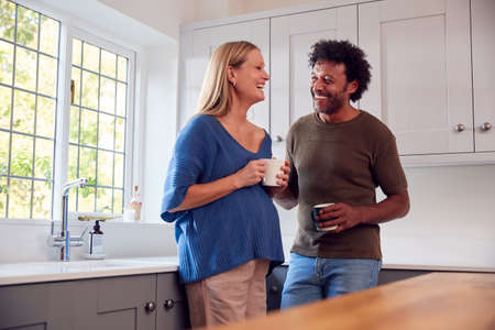 Couple With Pregnant Wife In Kitchen Talking And Drinking Coffee Together 스톡 콘텐츠