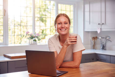 Portrait Of Mature Woman Wearing Fitness Clothing At Home In Kitchen Logging Activity On Laptop 스톡 콘텐츠