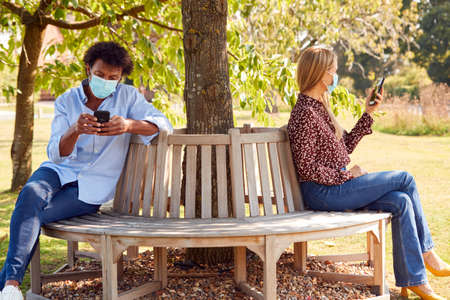 Couple Wearing Masks Meeting In Outdoor Park During Health Pandemic Looking At Mobile Phones