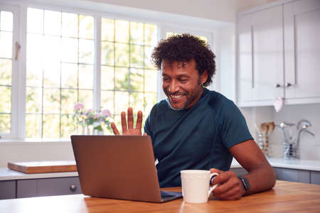 Mature Man At Home In Kitchen Waving As He Makes Video Call On Laptop Computer 스톡 콘텐츠