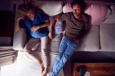 Overhead View Of Mature Couple With Pregnant Woman Relaxing On Sofa At Home Together