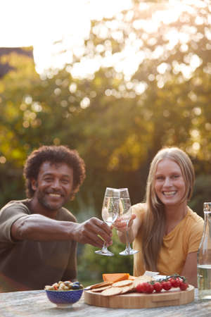 Portrait Of Mature Couple Celebrating With Champagne As They Sit At Table In Garden With Snacks
