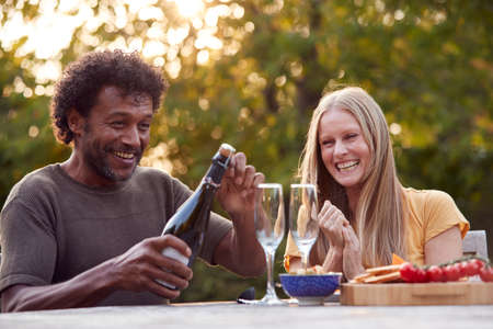 Mature Man Opening Champagne Bottle As Couple Celebrate Sitting At Table In Garden With Snacks