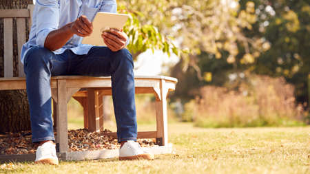 Close Up Of Man Sitting On Bench Under Tree In Summer Park Using Digital Tablet 스톡 콘텐츠