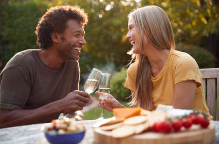 Mature Couple Celebrating With Champagne As They Sit At Table In Garden With Snacks 스톡 콘텐츠
