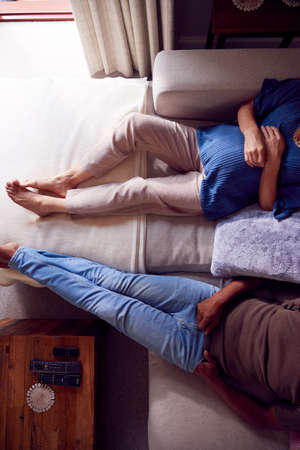 Close Up Overhead View Of Mature Couple With Pregnant Woman Relaxing On Sofa At Home Together 스톡 콘텐츠