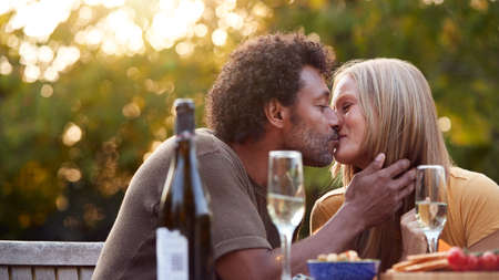 Mature Couple Kissing As They Celebrate With Champagne Sitting At Table In Garden With Snacks 스톡 콘텐츠
