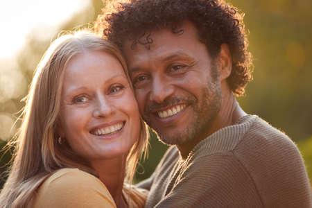 Portrait Of Loving Mature Couple Hugging Outdoors Against Flaring Evening Sun