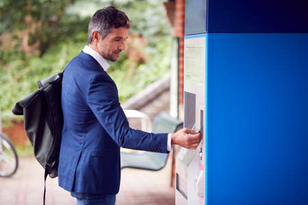 Businessman Commuting Making Contactless Payment For Train Ticket At Station Machine With Card