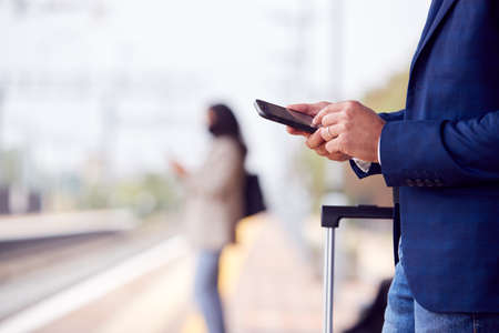 Close Up Of Businessman On Railway Platform Texting On Mobile Phone