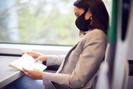 Businesswoman On Train Relaxing And Reading Book Wearing PPE Face Mask During Health Pandemic