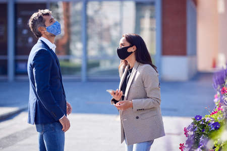 Businessman And Businesswoman Having Socially Distanced Meeting Outdoors In Street