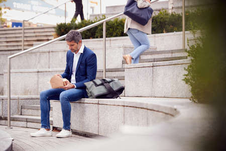 Businessman Sitting Outside On Lunch Break Eating Takeaway Meal From Sustainable Recyclable Carton
