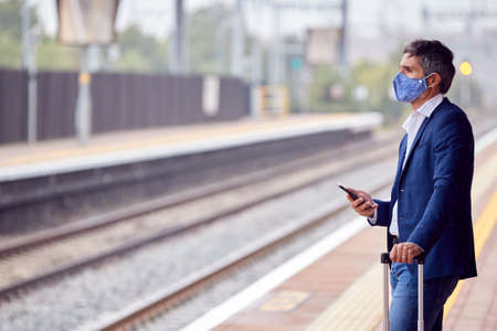 Businessman On Railway Platform With Mobile Phone Wearing PPE Face Mask During Health Pandemic 스톡 콘텐츠