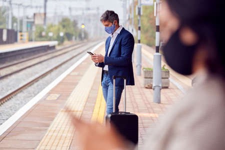 Business Commuters On Railway Platform With Mobile Phones Wearing PPE Face Masks During Pandemic