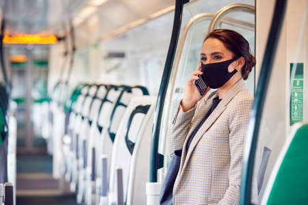 Businesswoman In Train Carriage Talking On Mobile Phone Wearing PPE Face Masks During Pandemic