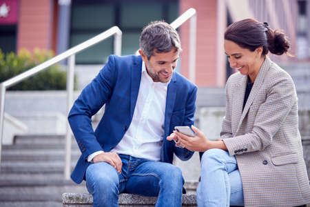 Businessman And Businesswoman Sitting By Steps Having Meeting Outdoors Looking At Phone 스톡 콘텐츠