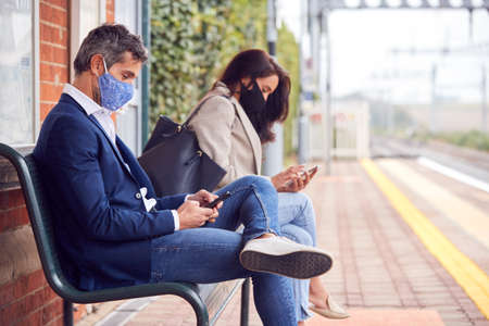 Business Commuters Sitting On Railway Platform With Mobile Phones Wearing Face Masks During Pandemic 스톡 콘텐츠