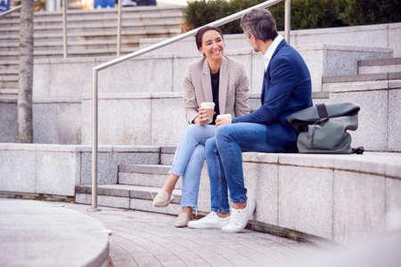 Businesswoman And Businessman Meeting Outside On Lunch Break Drinking Takeaway Coffee