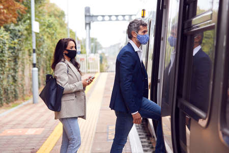 Two Business Commuters Wearing Face Masks Boarding Train At Platform During Pandemic 스톡 콘텐츠