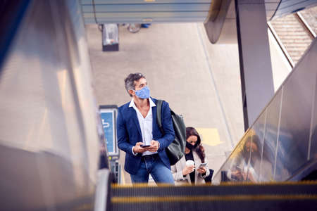 Business Commuters Riding Escalator At Railway Station Wearing PPE Face Masks In Pandemic