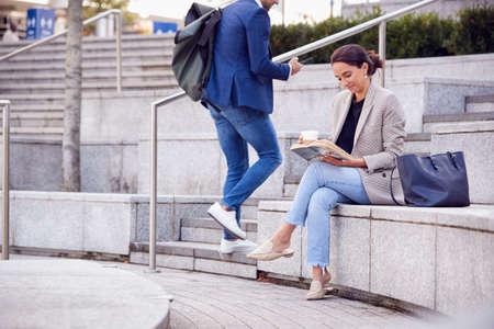 Businesswoman Sitting Outside On Lunch Break Reading Book And Drinking Takeaway Coffee