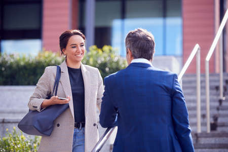 Businessman And Businesswoman Meeting Outdoors Standing On Steps And Talking
