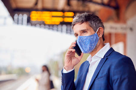 Businessman On Railway Platform Talking On Mobile Phone Wearing PPE Face Mask During Health Pandemic