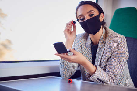 Businesswoman On Train Putting On Makeup Whilst Wearing PPE Face Mask During Health Pandemic