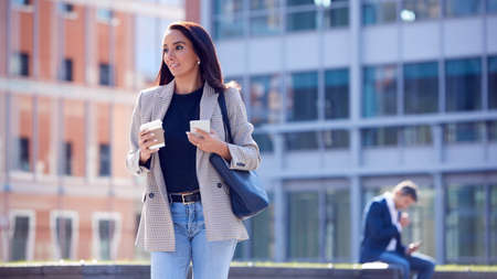 Businesswoman With Takeaway Coffee Walking To Office Holding Mobile Phone