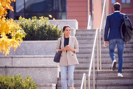 Businessman And Businesswoman Commuting Outdoors Passing On Steps On Way To Work