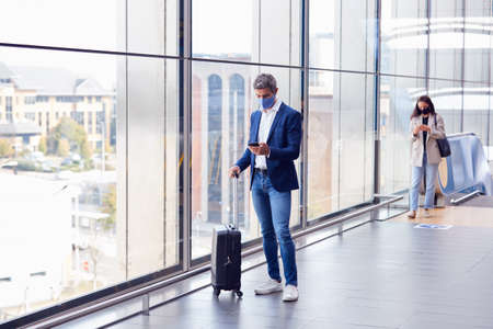 Businessman With Suitcase Standing By Window On Concourse At Railway Station With Mobile Phone