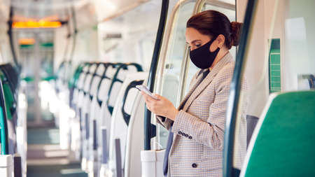 Businesswoman Stands In Train Carriage Using Mobile Phone Wearing PPE Face Masks During Pandemic