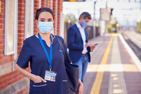 Portrait Of Nurse On Railway Platform Wearing PPE Face Mask Commuting To Work During Pandemic