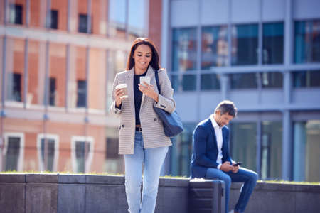 Businesswoman With Takeaway Coffee Walking To Office Looking At Mobile Phone 스톡 콘텐츠