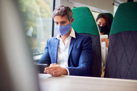 Businessman On Train Streaming To Mobile Phone Wearing PPE Face Mask During Health Pandemic