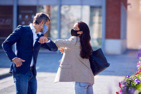 Businessman And Businesswoman Having Socially Distanced Meeting Outdoors Touching Elbows 스톡 콘텐츠