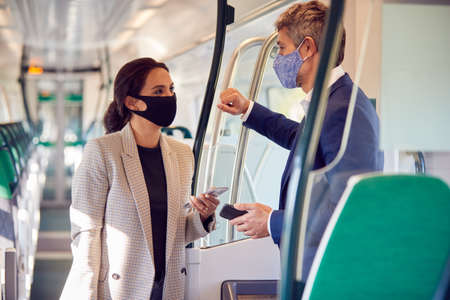 Business Commuters Stand In Train Carriage With Mobile Phones Wearing PPE Face Masks During Pandemic