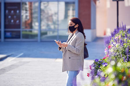 Businesswoman Wearing Mask Walking To Office Looking At Mobile Phone In Health Pandemic