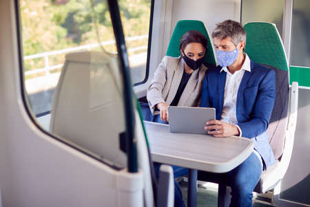 Businesswoman And Businessman On Train Using Digital Tablet Wearing PPE Face Mask During Pandemic