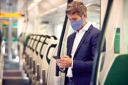 Businessman Stands In Train Carriage Using Mobile Phone Wearing PPE Face Masks During Pandemic 스톡 콘텐츠