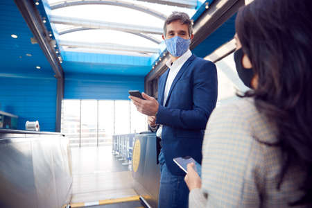 Business Couple Commuting Riding Escalator At Railway Station Wearing PPE Face Masks In Pandemic 스톡 콘텐츠