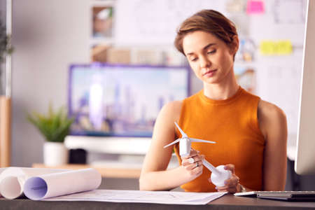 Female Architect In Office Working On Drawings For Renewable Energy Project With Model Wind Turbine