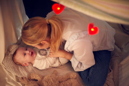 Loving Mother Cuddling Baby Son Lying On Blanket In Homemade Camp In Child's Bedroom At Home