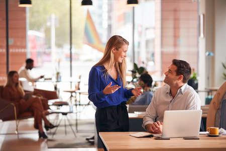 Businessman And Businesswoman Having Informal Meeting By Desk In Modern Open Plan Office