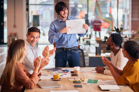 Colleagues Applauding As Businessman Gives Presentation In Modern Open Plan Office