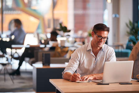 Businessman Sitting At Desk Writing In Notebook In Modern Open Plan Office