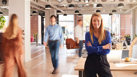 Portrait Of Businesswoman By Desk In Busy Multi-Cultural Office With Motion Blurred Colleagues